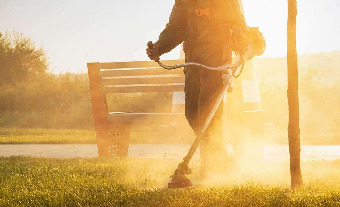 Άντρας με στολή εργασίας χρησιμοποιεί θαμνοκοπτικό για να κόψει βλάστηση