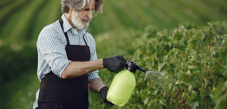 Άντρας αγρότης ψεκάζει με φάρμακο το χωράφι του για χημική καταπολέμηση ζιζανίων.